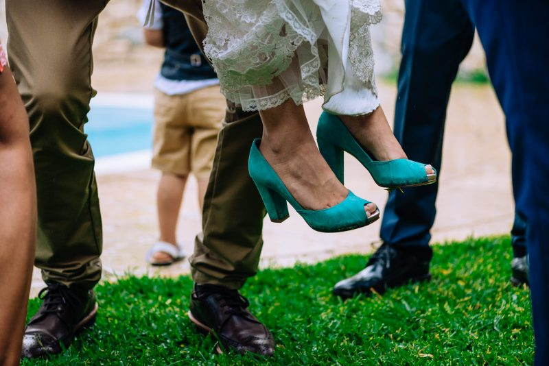 Bride lift up by friends on a rainy wedding day, detail of the wet wedding shoes