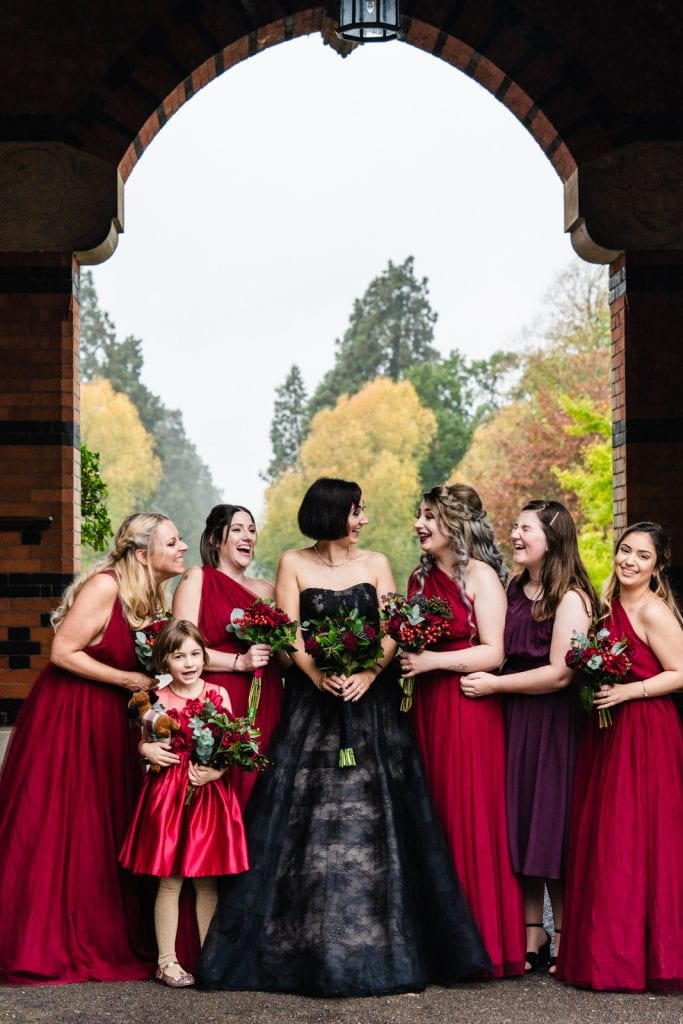 Bride in a black Vera Wang Dress with her bridesmaids wearing red dresses
